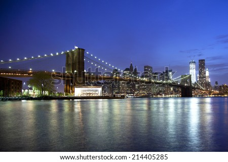 Brooklyn Bridge reflects off the water at night