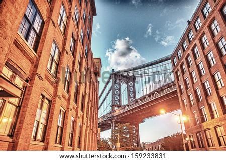 Brooklyn Bridge seen among city buildings at night. - stock photo