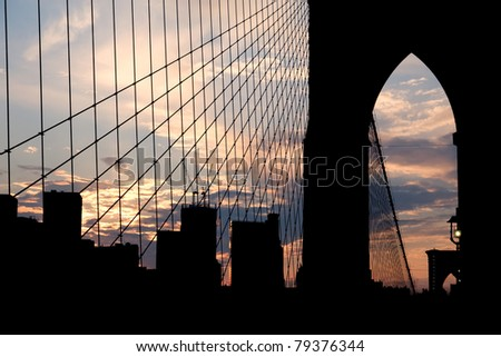 Brooklyn Bridge silhouette with subtle bridge lights, and Freedom Tower in the background - stock photo