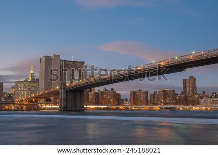 Brooklyn Bridge spanning the East River from Brooklyn into New York City at sundown
