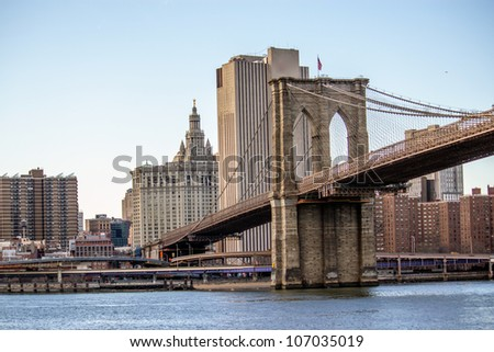 Brooklyn Bridge with  Manhattan skyline panorama in the afternoon with cloud and river reflection over East River in New York City - stock photo