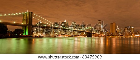Brooklyn Bridge with the skyline of New York in the background by night - stock photo