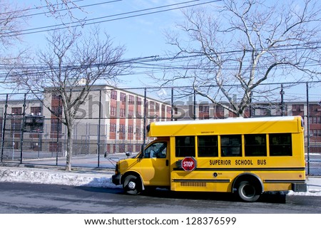 BROOKLYN, NEW YORK - FEBRUARY 14: School bus in front of public school in Brooklyn, NY on February 14, 2013. NYC School Bus Drivers union 1181 still on strike form January 16, 2013. - stock photo