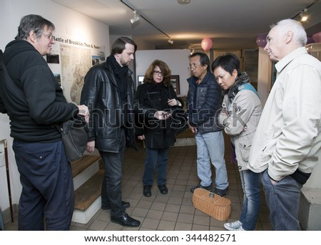 "BROOKLYN, NEW YORK, USA - NOVEMBER 22: Raymond Sawyers ""center left"" takes readings as  members of the borough paranormal meetup group investigate the Old Stone House.  Taken November 22, 2015 in NY. - stock photo"