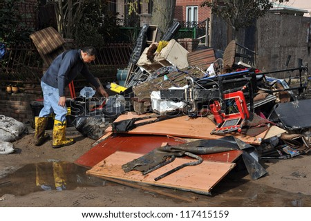 BROOKLYN, NY - NOVEMBER 01: People cleaning debris at the buildings at the Seagate neighborhood due to impact from Hurricane Sandy in Brooklyn, New York, U.S., on Thursday, November 01, 2012. - stock photo