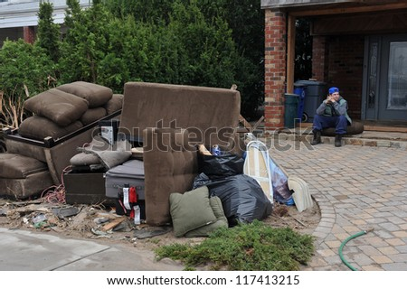 BROOKLYN, NY - NOVEMBER 01: Unknown person sitting sad by his house at the Seagate neighborhood due to impact from Hurricane Sandy in Brooklyn, New York, U.S., on Thursday, November 01, 2012. - stock photo
