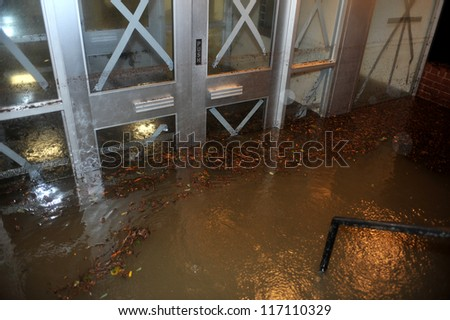 BROOKLYN, NY - OCTOBER 29: Flooded building entrance, caused by Hurricane Sandy, seen on October 29, 2012, in the corner of Bragg street and  Shore Pway of Brooklyn NY, United States. - stock photo