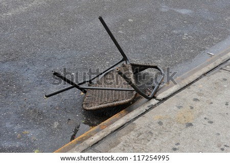 BROOKLYN, NY - OCTOBER 30: Smashed chair on the ground in the Sheapsheadbay neighborhood due to flooding from Hurricane Sandy in Brooklyn, New York, U.S., on Tuesday, October 30, 2012. - stock photo