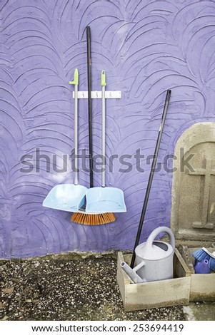 Broom and collectors hung on wall cleaning - stock photo