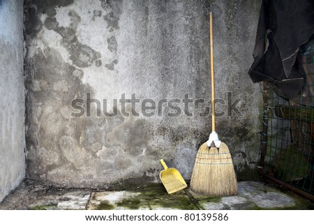 broom and dustpan leaning against a grunge wall