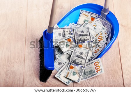 Broom sweeping dollars in scoop from on wooden floor, closeup - stock photo
