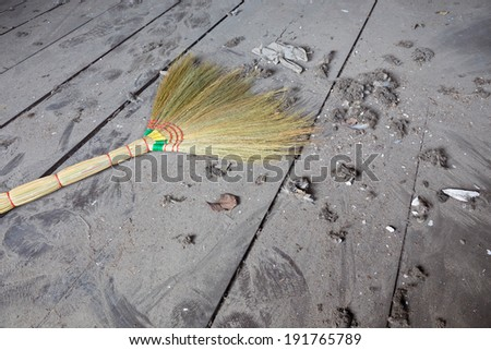 broom with gossamer on dirty floor - stock photo