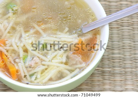 Broth soup with spoon with carrot, pea and noodles