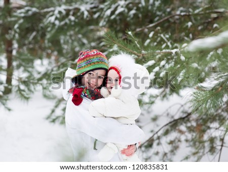 Brother and baby sister walking in a forest on a snowy winter day - stock photo