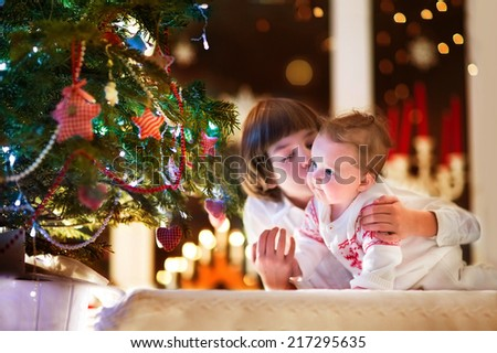 Brother and his baby sister playing together at a Christmas tree with colorful lights in a dark living room - stock photo