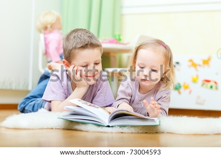 Brother and his little sister at home reading together - stock photo