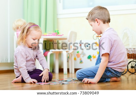 Brother and his little sister at home working on puzzle - stock photo