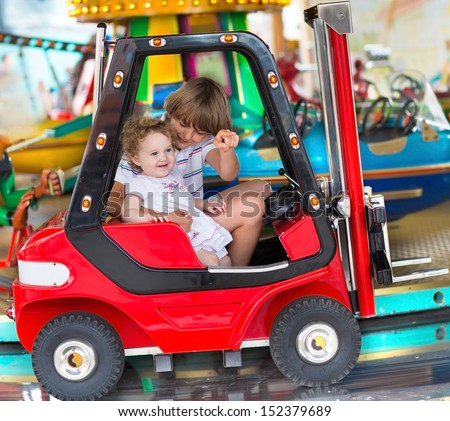 Brother and little baby sister enjoying a ride in an amusement park  - stock photo