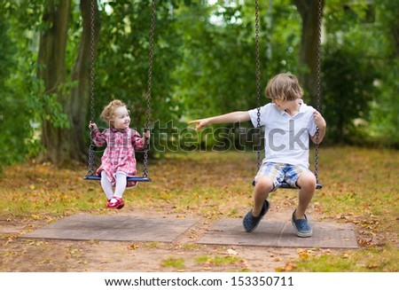 Brother and little baby sister playing together on a swing on a playground in a park on a warm nice autumn day - stock photo