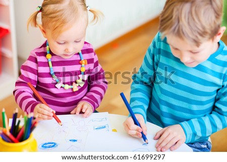 Brother and little sister drawing with coloring pencils in their room