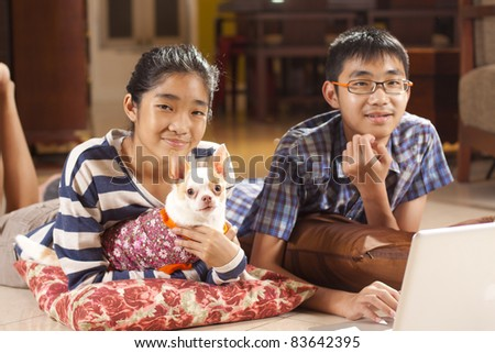 brother and sis, brother, sister and a dog playing notebook on floor. - stock photo