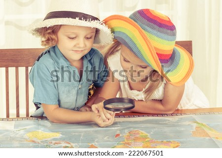 brother and sister are considering a world map with a magnifying glass at home - stock photo