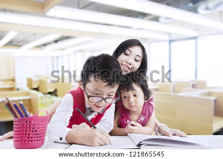 Brother and sister are drawing with their teacher in classroom - stock photo