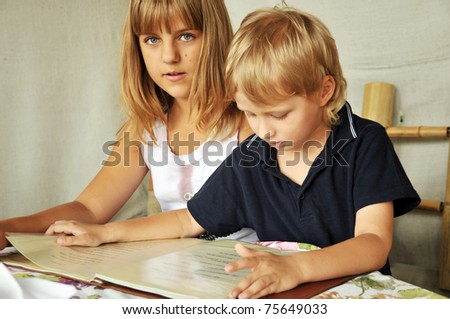 brother and sister are in the cafe reading menu card - stock photo