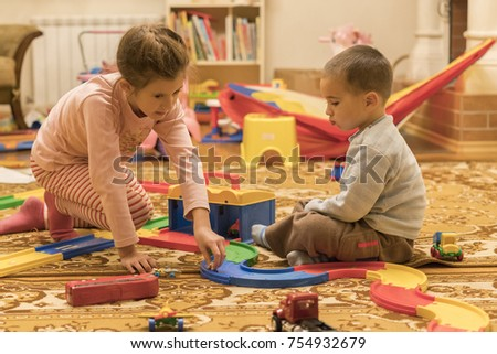 Brother and sister are playing cars in the room