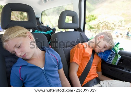 Brother and sister (8-12) asleep in back of car, close-up - stock photo