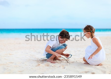 Brother and sister at beach enjoying vacation - stock photo