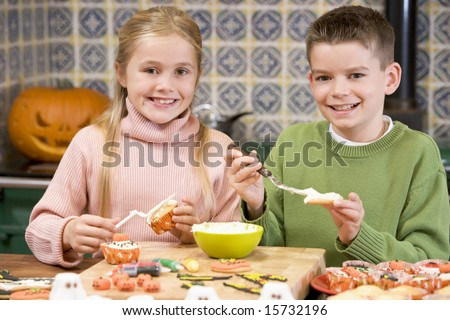 Brother and sister at Halloween making treats and smiling - stock photo