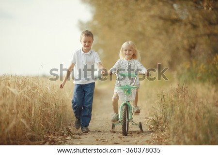 brother and sister Autumn road bicycle - stock photo