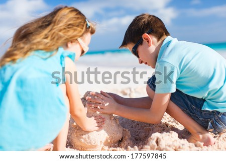 Brother and sister building sand castle at tropical beach