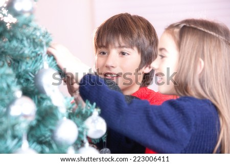 Brother and sister celebrating Christmas at home near tree. - stock photo
