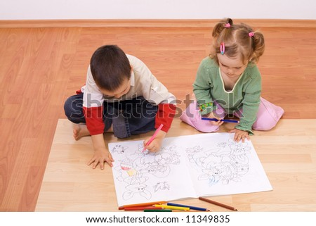 Brother and sister coloring the tale book - stock photo