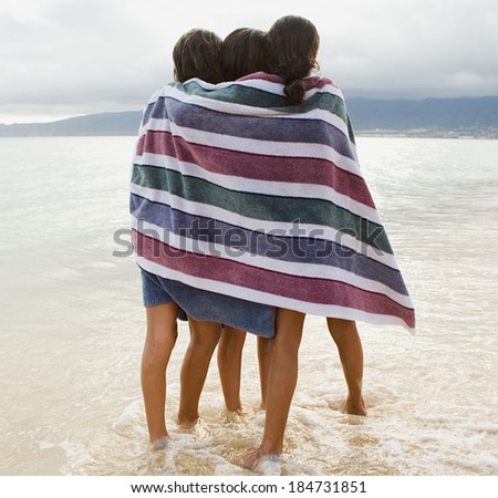 Brother and sister cuddling in a towel  - stock photo