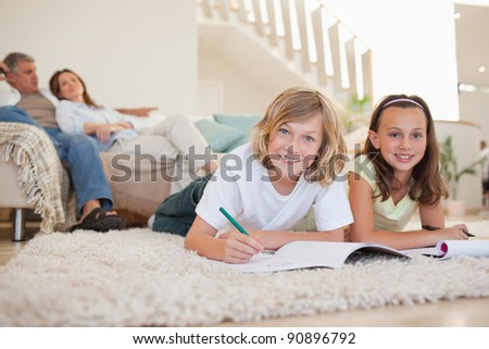 Brother and sister doing their homework on the floor - stock photo