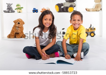 brother and sister drawing on book - stock photo
