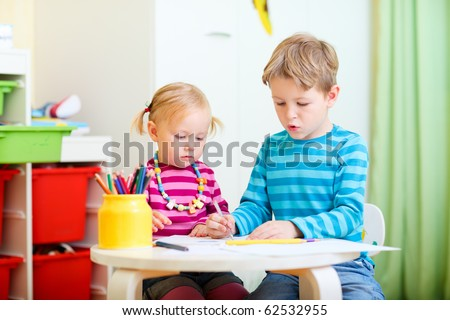 Brother and sister drawing together with coloring pencils - stock photo