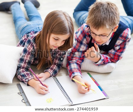 Brother and sister drawing with crayons in living room - stock photo