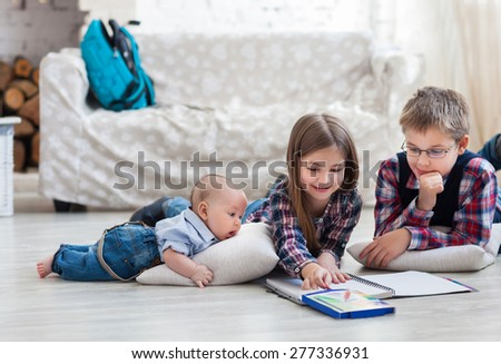Brother and sister drawing with crayons in living room with baby brother - stock photo