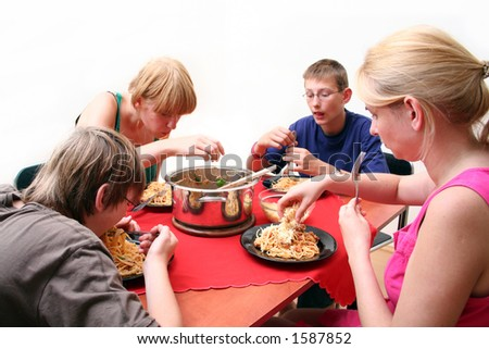 Brother and sister eat spaghetti - stock photo