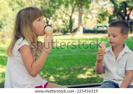 Brother and sister eating icecream on sunny summer day. - stock photo