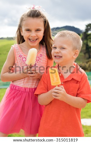 Brother and sister eating popsicles - stock photo
