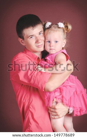 Brother and sister embracing each other. Handsome teenager posing in studio with his little sister.Happy brother and baby sister smiling. Funny lovely child in trendy wear in the arms of her brother - stock photo