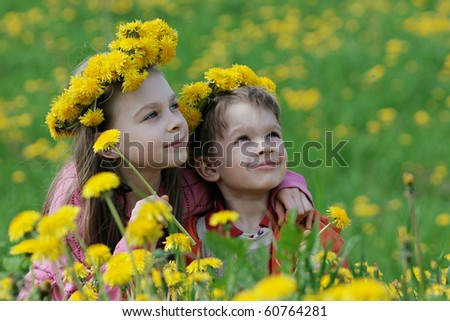 Brother and sister enjoy summer time in the dandelion meadow. - stock photo