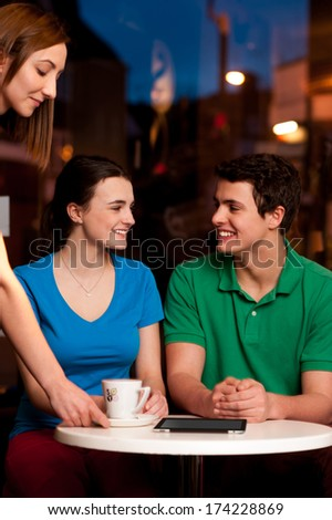Brother and sister enjoying the coffee in cafe - stock photo