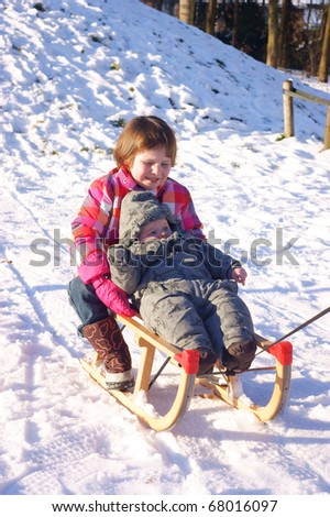 Brother and sister enjoying the snow together - stock photo