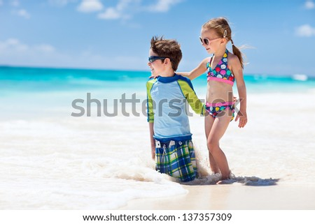Brother and sister enjoying time at tropical beach - stock photo